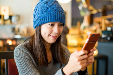 use: Woman look at her phone at coffee shop Stock Photo