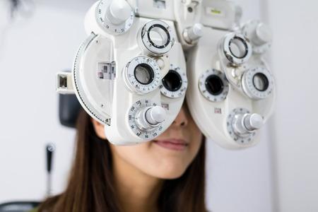 Vrouw doet gezichtsvermogen meting met optische phoropter