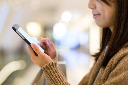 centro comercial: Mujer que usa el teléfono celular en un centro comercial Foto de archivo