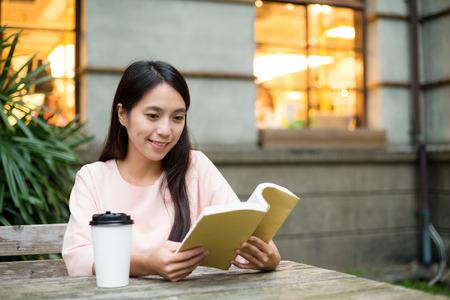 Woman reading boo at outdoor cafe Foto de archivo
