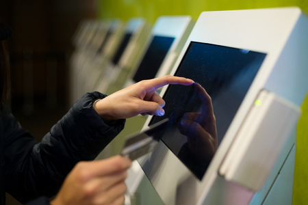ticketing: Woman touch on screen of automatic ticketing system Stock Photo