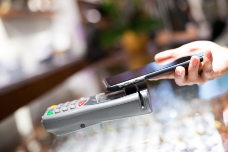 paying: Woman paying through smartphone using NFC technology