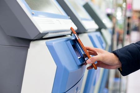 Frau bezahlt mit Handy von NFC auf Ticketing-System Standard-Bild