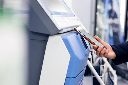 La donna paga con il cellulare da NFC sul terminale di biglietteria