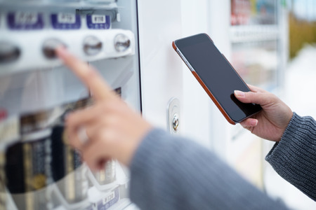 Woman use of soft drink vending system paying by cellphone Archivio Fotografico