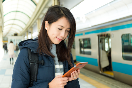 woman at the phone: Woman use smart phone at train platform