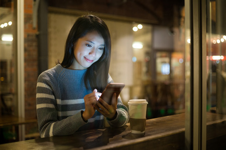 女性のコーヒー ショップで携帯電話を使用して