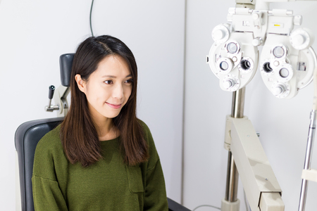 optician: Optician in surgery giving woman eye test