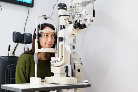 examenes de laboratorio: Mujer que mira en la máquina de prueba del ojo