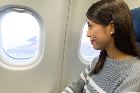 Woman looking out of the window in airplane Imagens