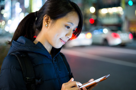 message sending: Woman sending text message on cellphone in Tokyo city at night Stock Photo