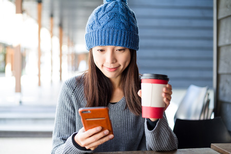 japanese people: Woman look at cellphone at outdoor cafe Stock Photo