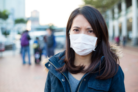 deterrence: Woman wear face mask in pollution city Stock Photo