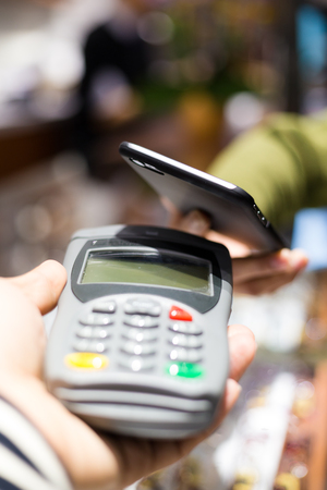 nfc: Customer paying with NFC technology on smart phone
