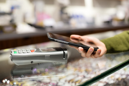 wireless terminals: Woman pay by mobile phone with NFC