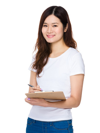 jot: Asian woman jot down the note on clipboard Stock Photo