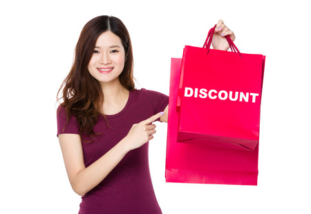 t off: Asian woman with finger point to shopping bag and showing a word discount