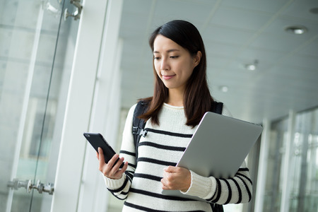 Woman hold with laptop ccomputer and look at cellphone