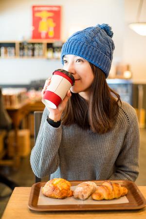 comiendo pan: La mujer disfruta de su café de la mañana