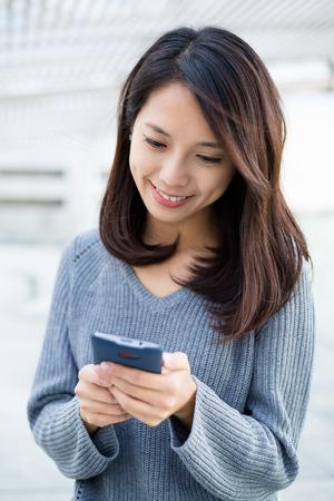 uso de la mujer del teléfono inteligente al aire libre