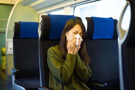 estornudo: Mujer estornudo cubierto por el tejido en el compartimiento del tren
