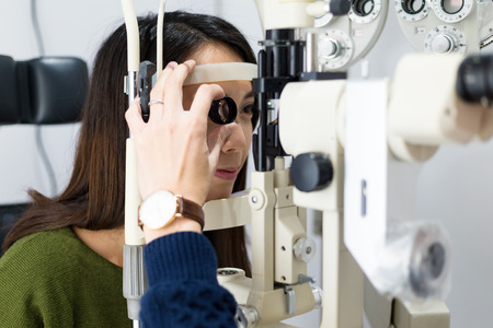 Woman having her eyes examined by eye doctor 免版税图像