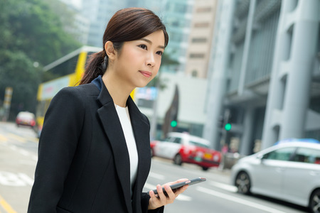 look for: Businesswoman standing beside the street and look for a taxi