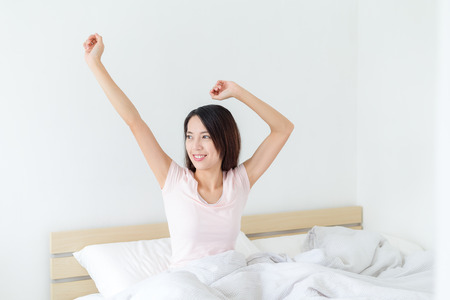 sitting up: Young woman waking up happily