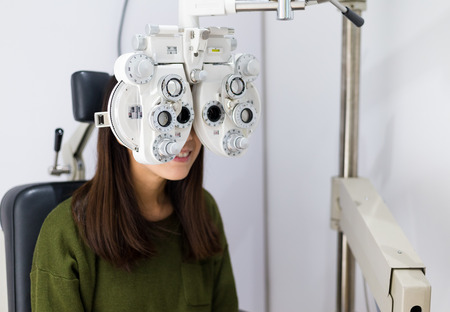 diopter: Woman checking on her eye with optometry machine Stock Photo