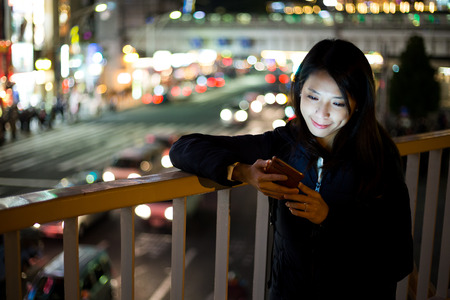 asian working woman: Woman use of smart phone at night in Tokyo