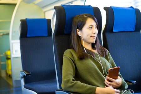 earphone: Woman listen to music on mobile phone inside train compartment