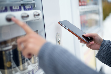 machine: Woman using cellphone to pay the vending machine
