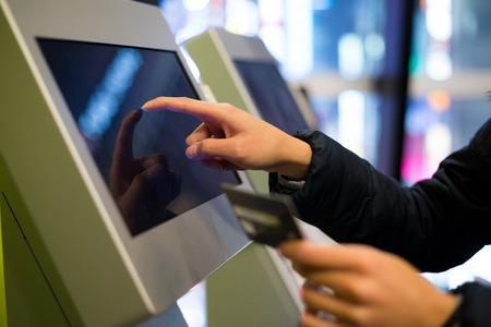 Frau mit Kreditkarte über die automatische Kino-Ticketing Terminal zu bezahlen