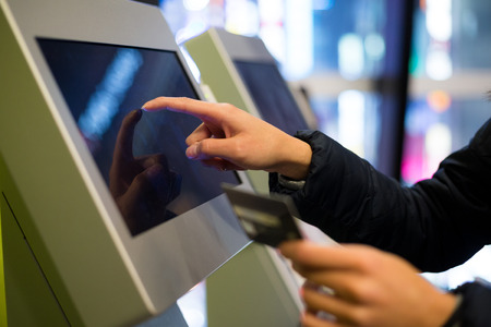 ticketing: Woman using credit card to pay on the automatic cinema ticketing terminal