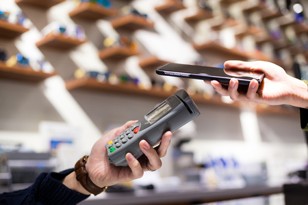 wireless terminals: Woman pay by cellphone with NFC Stock Photo