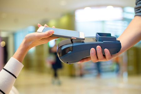 wireless terminals: Woman paying on cellphone by NFC inside shopping mall