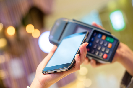 checkout button: Woman pay with cellphone by NFC technology Stock Photo