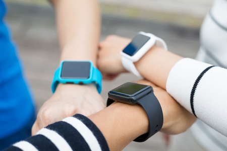 group of hands: Group of people wearing smartwatch