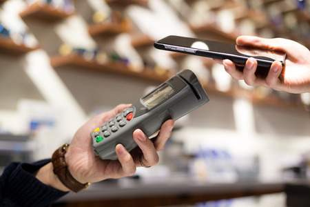 paying: Woman paying with NFC technology on mobile phone in shop