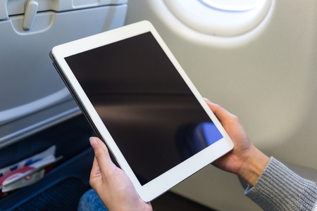 compartment: Woman use of tablet computer inside airplane