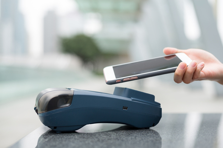 wireless terminals: Woman pay by mobile phone with NFC technology