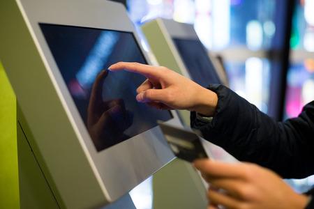 Vrouw die bij kaartjesmachine in bioskoop betaalt