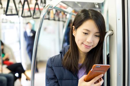 女性列車コンパートメントの中の携帯電話の使用