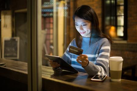 女性は、タブレット pc のクレジット カードを支払う
