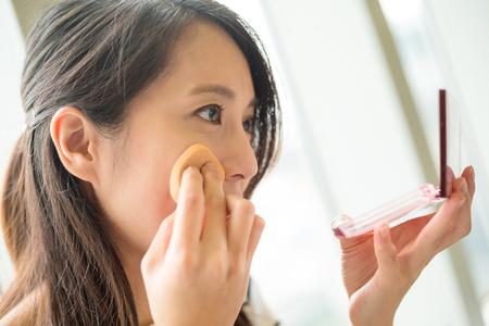 Vrouw met behulp van poeder aan te raken up op haar gezicht Stockfoto
