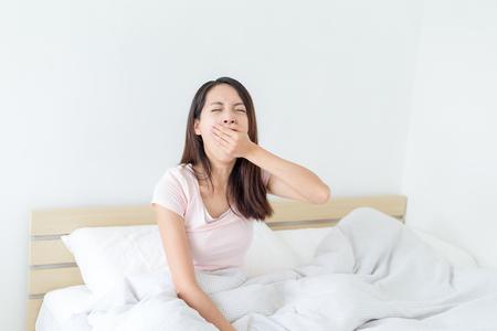 wellness sleepy: Woman yawning at bed