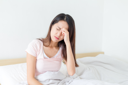 suffer: Woman suffer from headahce and sitting on bed