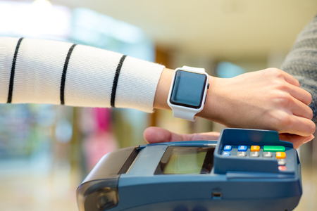 nfc: Customer using smartwatch to pay the bill by NFC technology
