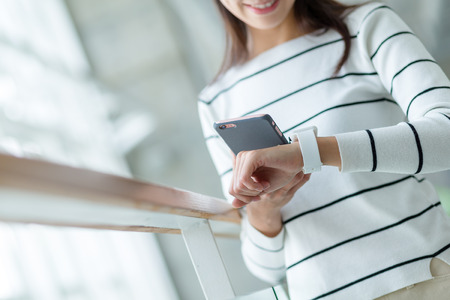 sync: Woman using wearable watch connecting to cellphone