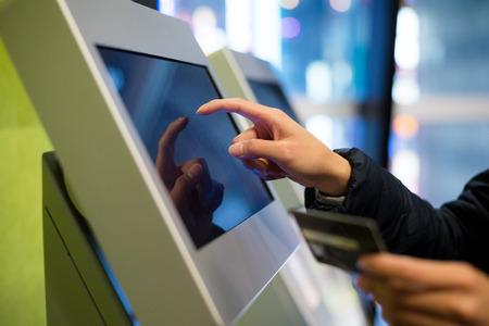 ticketing: Woman using credit card on automatic ticketing machine